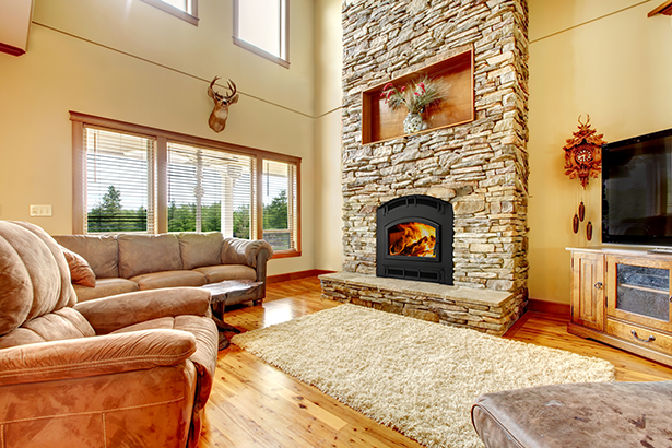 Living room with hard wood floors and a beautiful Pioneer III fireplace with stone surround.